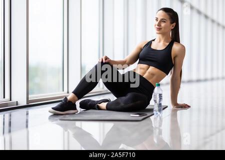 Portrait von Frau Rest nach Training. Müde und weiblichen Athleten sitzen auf dem Boden im Fitnessstudio erschöpft. - Stockfoto
