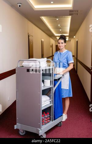 Hübsche junge Zimmermädchen in Uniform stehen in langen Korridor, saubere Handtücher und andere Sachen im Hotel Zimmer - Stockfoto