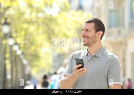 Glücklich der Mensch sieht auf Seite Holding smart phone auf der Straße - Stockfoto