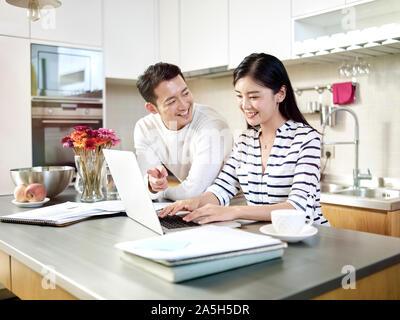 Glückliche junge asiatische Paar zusammen arbeiten von zu Hause aus Sprechen, Diskutieren mit Laptop in der Küche - Stockfoto