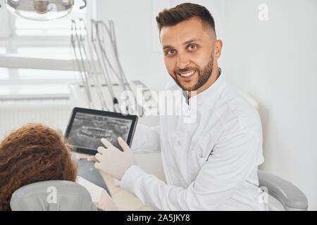Vorderansicht des positiven männlichen Zahnarzt tragen weiße Uniform an Kamera suchen und lächelnd, während Consulting weiblichen Patienten. Mann, der Tablet-PC mit x-ray Bild der Zähne. Konzept der Pflege und Gesundheit. - Stockfoto