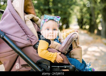 Happy girl im Kinderwagen im Pram spielen auf Hintergrund Natur. Portrait süße kleine schöne Mädchen von 9 Monaten sitzen oder Kinderwagen und Warten Stockfoto