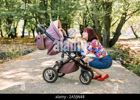 Junge Mutter ihr Kind in einem Kinderwagen zu betrachten