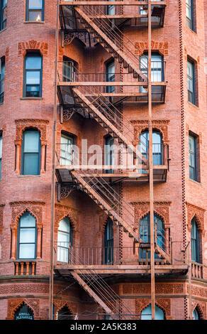 Typische externe Metall Notausgang Leitern auf ein rotes Backsteingebäude in der Back Bay von Boston, Massachusetts, New England, USA - Stockfoto