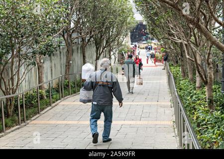 Ein chinesischer Mann Spaziergänge durch die Yuen Po Street Bird Garden mit seinem Käfig Singvögel, Mong Kok, Kowloon, Hong Kong. - Stockfoto