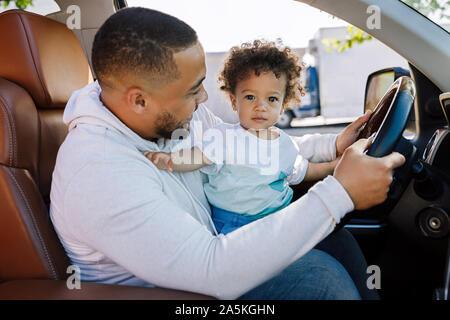 Schuss eine entzückende kleine Junge sitzt auf dem Schoß seines Vaters in ein Auto, und wenn man die Kamera - Stockfoto