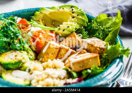 Buddha Schüssel mit Quinoa, Tofu, Avocado, süsse Kartoffeln, Rosenkohl und Pistazien. Gesunde vegane Ernährung Konzept. - Stockfoto