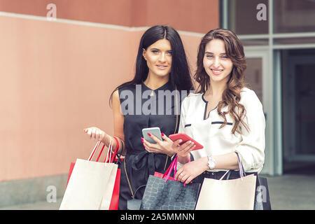 Zwei modischen Frauen suchen Bei camera mit Smartphones und Einkaufstaschen am Mall. Zwei Mädchen schaut die Kamera auf Shopping. - Stockfoto