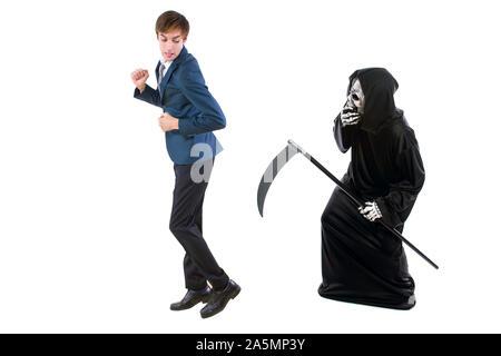 Mann in einem Halloween Sensenmann ghost Kostüm jagen, verspotteten und macht sich lustig über Angst Geschäftsmann weg laufen. Auch Tod zeigen nach einer Ma - Stockfoto