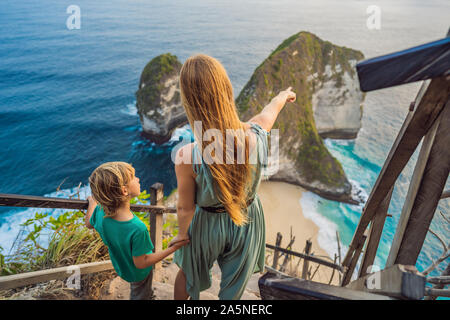 Familienurlaub Lebensstil. Glückliche Mutter und Sohn stehen im Blickpunkt. Am schönen Strand unter hohen Klippe. Reiseziel in Bali. Beliebte