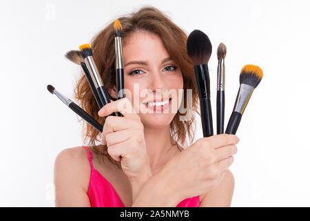 Junge schöne Mädchen mit gewellten braunen Haare, Haut, Zähne, schönes Lächeln, im rosa Trikot, hält eine Vielzahl von Make-up-Pinsel und Lächeln - Stockfoto