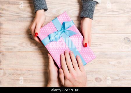 Blick von oben auf einen Mann und eine Frau gegenseitig gratulieren mit einem Geschenk auf Holz- Hintergrund. Überraschung für einen Urlaub. Close Up. - Stockfoto