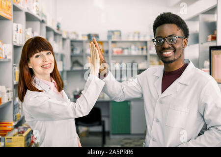 Zwei glückliche Kollegen Pharmazeuten, afrikanischer Mann und kaukasische Frau in der Apotheke arbeiten, lächelnd. Fünf und Spaß haben.
