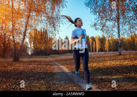 Runner Training im Herbst Park. Frau mit Wasserflasche und fit bleiben bei Sonnenuntergang. Aktiver Lebensstil. Training