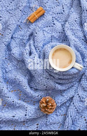 Tasse Kaffee auf gemütlichen blauen gestrickte Decke mit Pine Cone und Zimt. Winter Stimmung Komposition. Ansicht von oben, flach - Stockfoto