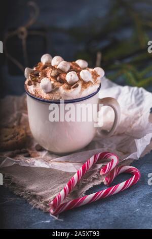 Luxuriöse heiße Schokolade mit Sahne und Stücke von Marshmallows und Chocolate Chips, in eine weiße Tasse auf einem blauen Hintergrund. Vor dem chocol - Stockfoto