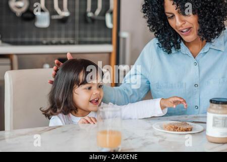 Lächelnd kleine Mädchen zu frühstücken, mit ihrer Mama zu Hause - Stockfoto