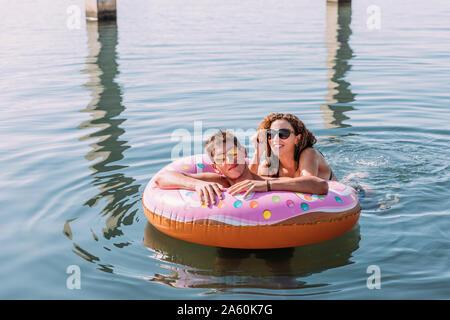 Junges Paar, das Baden im Meer auf aufblasbaren Schwimmer in Donut Form - Stockfoto
