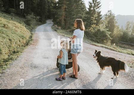 Mutter mit Tochter, Kinderwagen und Hund stehen auf Waldweg - Stockfoto