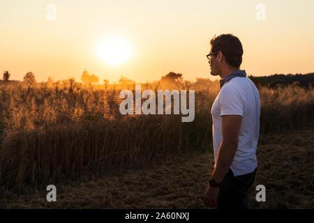 Biobauern über Weizenfeld bei Sonnenuntergang - Stockfoto