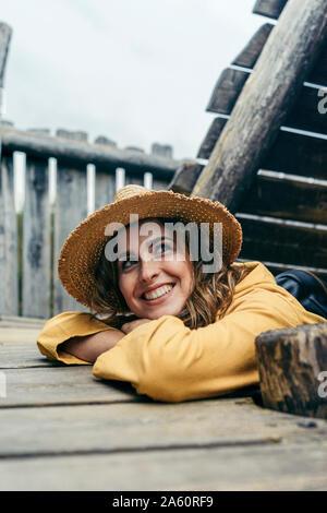 Junge lächelnde Frau mit gelben Mantel und Hut auf Holztreppen, seitlich auf der Suche - Stockfoto