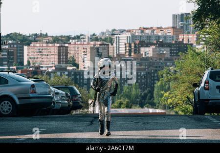 Junge gekleidet wie ein Astronaut zu Fuß auf einer Straße in der Stadt