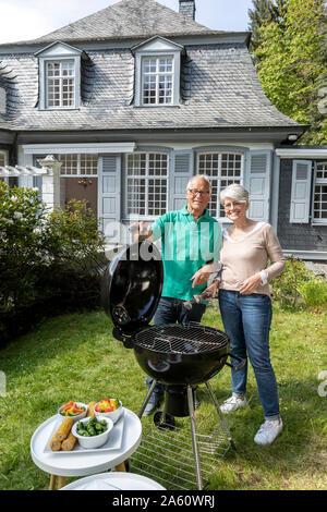 Gerne älteres Paar grillen im Garten ihres Hauses - Stockfoto