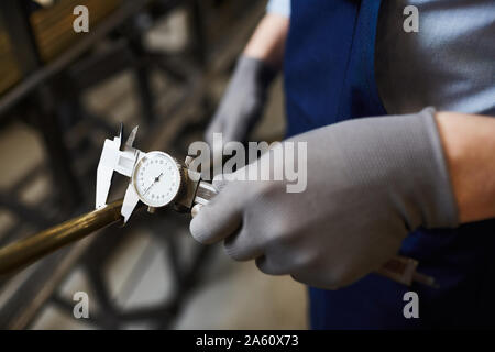 Nahaufnahme der Arbeiter in Schutzhandschuhe Holding eiserne Leitung und messen mit speziellen Instrument der Messung - Stockfoto