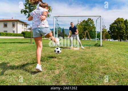 Vater und Tochter Fußball spielen auf einer Wiese - Stockfoto
