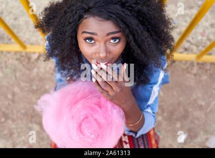 Porträt der jungen Frau mit rosa Zuckerwatte Stockfoto