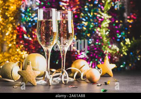 Champagner in zwei Gläser goldene Weihnachten Spielzeug Serpentine star Kugeln auf einem hellen festlichen Hintergrund. Neues Jahr Weihnachten Konzept. Horizontale Rahmen. - Stockfoto