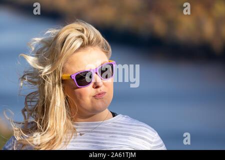 Blonde Frau mit gespitzten Lippen sieht in der Ferne, auf der Suche, zornig und fragwürdige - Stockfoto