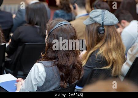Mann mit Headset auf der Konferenz. Kopf Telefon für Übersetzung online. Nicht erkennbare Personen mit in ear Kopfhörer für Übersetzung während der Veranstaltung - Stockfoto