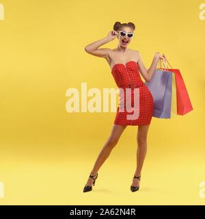 Glückliches Mädchen im roten Kleid und Sonnenbrille holding Einkaufstaschen auf gelbem Hintergrund - Stockfoto