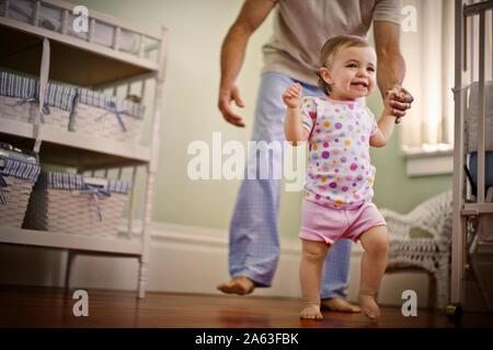 Vater helfen, seine Tochter ihre ersten Schritte machen - Stockfoto