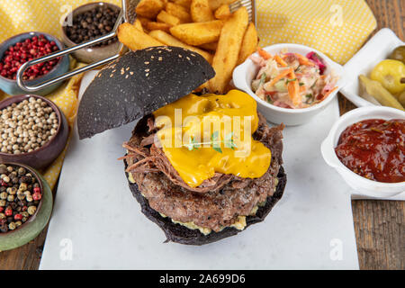 Beef Burger mit einem schwarzen Bun, mit Salat und Mayonnaise und Ketchup auf einem Stück braunem Papier auf einem rustikalen Holztisch von Zähler diente, auf einem dunklen Ba - Stockfoto