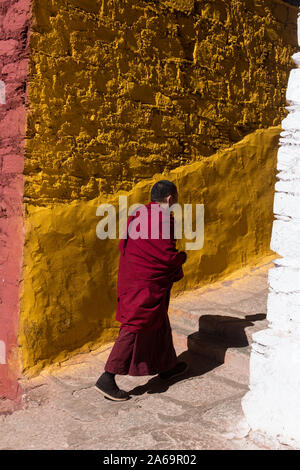 Ein buddhistischer Mönch geht die gelbe Serdung Lhakhang Gebäude des Klosters Ganden auf Wangbur Mountain in Tibet. - Stockfoto