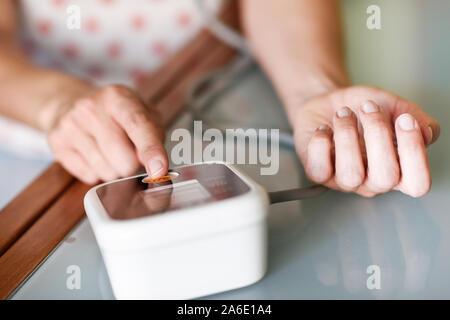 Frau messen Ihren Blutdruck zu Hause. - Stockfoto