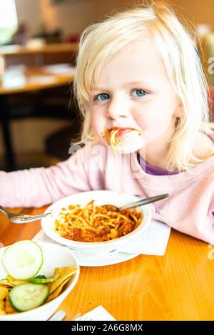 Eine schöne, süße kleine blonde Mädchen Spaß haben beim Essen Spaghetti Bolognese, spagbol in einem Restaurant - Stockfoto