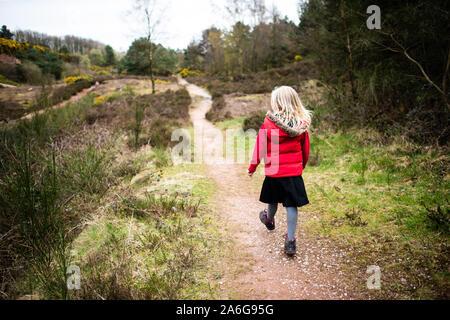 Hübsches kleines Mädchen springen in sehr schlammigen Pfütze das Spielen mit Ihrem Hund in der kalten Herbst Wetter in Stoke-on-Trent, Staffordshire, Hulme Steinbruch - Stockfoto