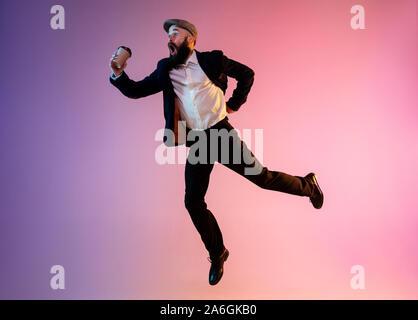 Volle Länge Portrait von Happy jumping Mann, Büro Kleidung im Neonlicht auf Farbübergang Hintergrund isoliert. Emotionen, Ad-Konzept. Sich beeilen, zu spät zur Arbeit oder Verkauf, shopping. Getränke Kaffee trinken gehen. - Stockfoto