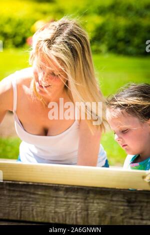 Eine hübsche Mutter in Ihrem 40 Knuddel spielen mit ihrer Tochter im Park, das Spielen mit Sand Burgen, ihren Druck auf die Schaukeln, Trentham Gardens - Stockfoto