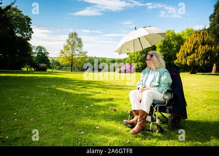 Eine behinderte Frau sitzt in Ihrem Rollstuhl an einem heißen Sommertag unter einem Sonnenschirm Ihr kühl zu halten und im Schatten, Schlaganfall, Herzinfarkt, Krankheit - Stockfoto