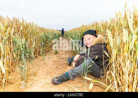 Ein kleiner Junge sitzt in einem Maisfeld tragen eine Baseballmütze, beim Spielen mit Freunden Stockfoto