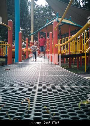 Asiatische Kleinkind spielen auf dem Spielplatz Reiten laufen und Lachen im Park. - Stockfoto