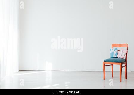 Stuhl mit Geburtstagsgeschenk in das Innere des weißen Zimmer - Stockfoto