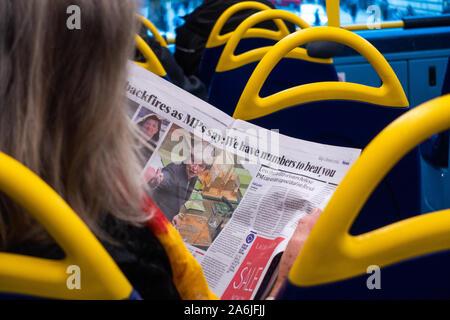 Ansicht der Rückseite des junge Frau sitzt beim Lesen einer Zeitung auf ein Bus - Stockfoto