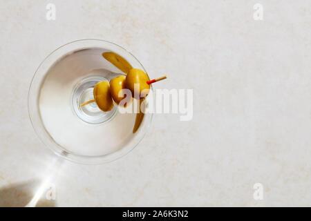 Glas trockener Martini mit Oliven unter harten Sommer Sonnenlicht. Ansicht von oben mit kopieren. - Stockfoto