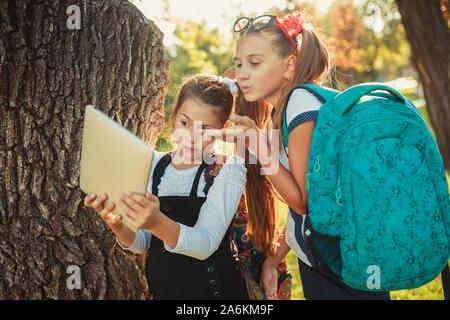 Zwei charmante schulpflichtigen Mädchen stehen durch den Baum neben der Schule und Spielen auf dem Tablett. Schülerinnen nehmen eine selfie - Stockfoto