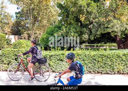Valencia Spanien Trinitat Jardines del Real Jardins del Reial Viveros Royal Garden städtischen öffentlichen Park garten landschaft Frau junge Reiten Fahrrad Helm Mutter Sohn asiatischen Spanisch Europa EU Eurozone - Stockfoto